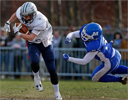 Dracut quarterback Matt Silva broke free of a first quarter tackle attempt by Methuen's Mike Harper. Silva led Dracut to the Thanksgiving Day victory.