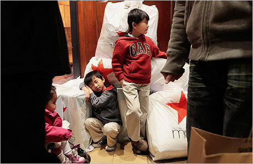 Children waited with shopping bags inside Macy's in New York City.