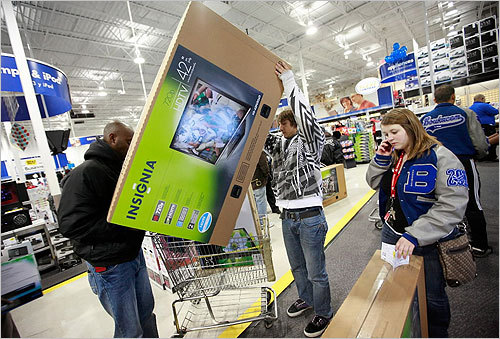 From left, Diman Mande, Daniel Herfeldt, and Sylvia Herfeldt secured a 42-inch flat screen TV while shopping at Best Buy in Fort Worth.
