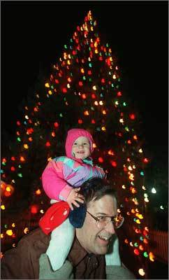 1995 Molly Shea, 2, of Hopkinton, rides atop her father Bob's shoulders after the tree was lit. It was Shea's first time seeing the tree lit.