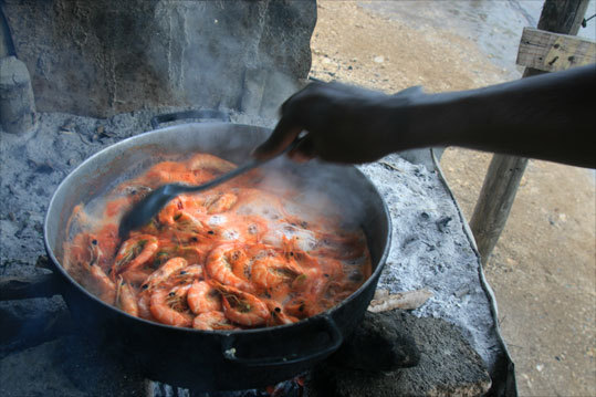 A cook sets a pot of Black River shrimp to boil on a Pimento wood fire.