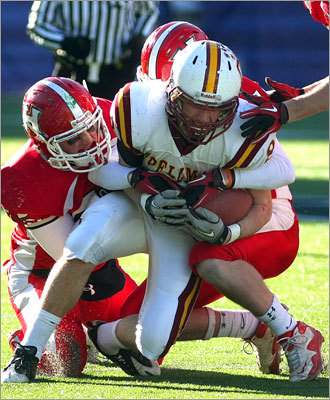 Spellman's Kevin Crane was wrapped up after a short gain by Holliston's David Kriegsman (left) brought him down.