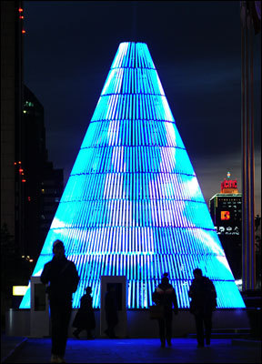 China Pedestrians walk past a neon-lit Christmas tree at twilight in Beijing.