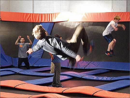 Pictured right is Jonathan Comeau, 23, of Somerville, executing a backflip on Sky Zone's large court. Sky Zone relies on constant monitoring and a strictly observed set of rules to further enhance safety.