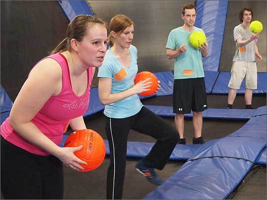 Alana Nagle, 30; Hannah Larsen, 29; Thomas Burdette, 21; and Donald Campbell, 24 listen attentively as a court monitor explains the dodgeball rules. The dodgeball court is a smaller, 2,600-square-foot network of trampolines. The largest trampoline court is 6,450 square feet.