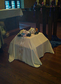 One white cloth covered two tiny caskets, each topped with a spray of fresh flowers and a small stuffed bear.