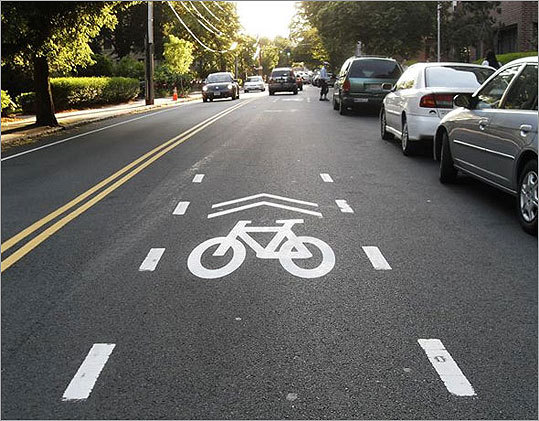 On Longwood Avenue, <a href=' http://www.boston.com/yourtown/news/brookline/2010/06/on_biking_a_ride_on_a_bicycle.html'>bikers will find bicycle priority lanes. A professor of engineering at Northeastern University, Peter Furth, came up with the idea. He offers an explanation of the new concept by comparing it with priority seating on the T: &#147; If there are no bikes, then cars can proceed as usual, but if you&#146;re biking then you&#146;re entitled to pedal in the middle of the lane, well away from parked cars and in a position that makes it safer to ride.&#148; At left, the new symbol on Longwood Avenue.