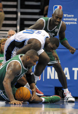 Davis (bottom), Bass (center), and Kevin Garnett battled for a loose ball during the first half.
