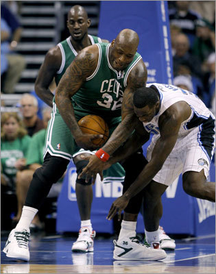 Shaquille O'Neal held the ball as Bass tried to get it during the first half.
