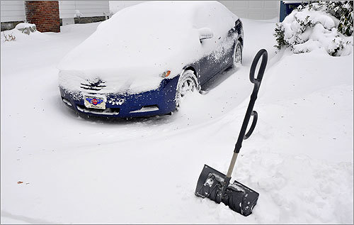 A shovel in West Roxbury waited in the snow next to a car for someone to use it.