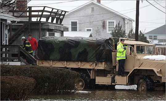 Scituate Police Lt. Mike Stewart guides a National Guard truck to make a rescue. Scituate Police Lieutenant Ted Coyle said the Massachusetts National Guard had been brought in to help with evacuations.