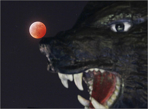 The lunar eclipse as viewed behind a carving of a bear at a souvenir shop in Japan.