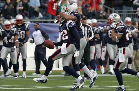 Patriots linebacker Jerod Mayo (center) hugged cornerback Devin McCourty (left) after McCourty intercepted a pass in the first quarter. The pick was McCourty's seventh of the season. The Patriots beat the Dolphins 38-7 Sunday to finish the regular season with a 14-2 record.