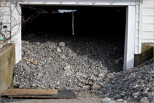 Passersby gawked at one garage filled almost to its ceiling with stones. One family was excavating their basement, hauling out bikes, mattresses, and a waterlogged washing machine into the cold air outside. Residents uneasily joked about another storm that could hit Friday.