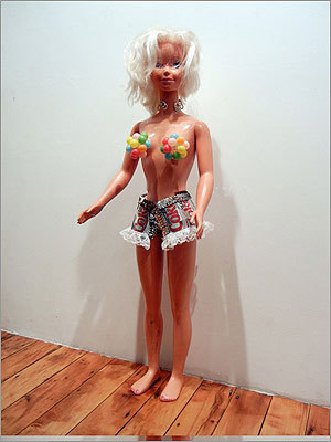 "Vanessa R. Thompson is a mixed-media artist who combines found objects and her original creations to explore the twisted subtexts of children's toys and activities. Her sculpture ""Refreshing"" combines a child-sized doll with very grown-up proportions with items that reflect the commodification and sexualization of such female figures."