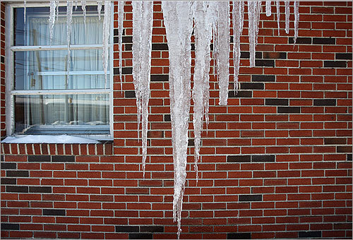 Long icicles hanged from a brick wall in Framingham.