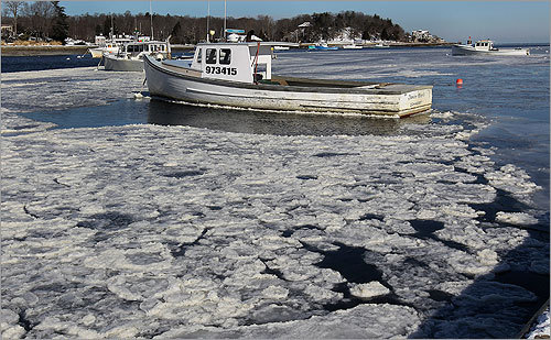 A lobster boat was anchored and going nowhere in frozen Cohasset Harbor.