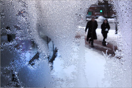 A couple walked past an iced over window as seen from inside Exotic Flowers at Faneuil Hall.