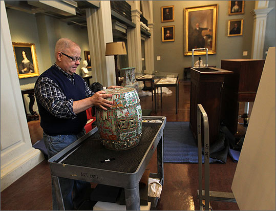David Dearinger, chief curator of art collection, moves an art object.