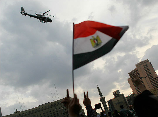 Egyptians shouted, waved flags, and gestured at an Egyptian Army helicopter buzzing over Tahrir Square on Sunday.