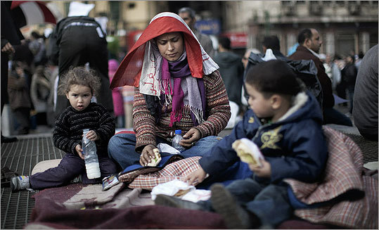 An Egyptian mother sat with her children on the aeration grid of the Cairo metro in Tahrir Square, in central Cairo on Sunday.