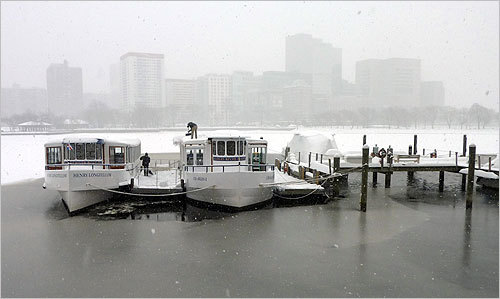 From left, Lou Beaulieu, marine manager of Charles Riverboat Company, and Tom Culbertson, operations manager, cleared snow off their boats. Although they don't resume tours until April, they remove the snow from the boats to prevent the flat roofs from collapsing.