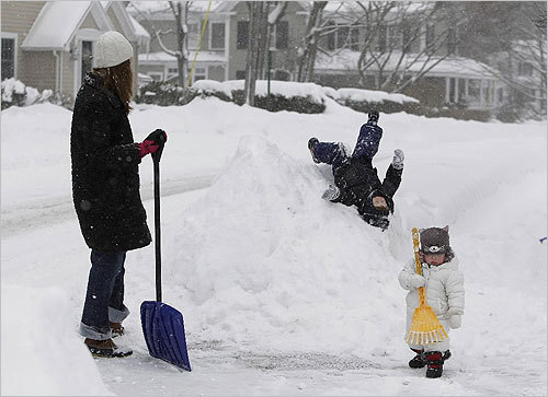 William Chisholm, 2, slid down a snow bank in front of his house as his mother, Tara, and his younger sister Ilona, raked snow in Cohasset on Tuesday.