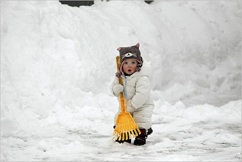 Ilona Chisholm, 13 months, helped her mom shovel snow out of their driveway in Cohasset on Tuesday.