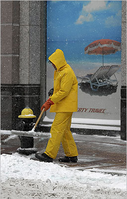Joseph Kaplan swept snow from the sidewalk at the State Street Financial Center by Bedford Street in Boston on Tuesday.