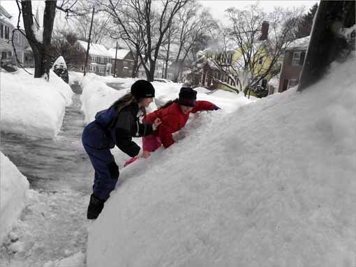 Colette O'Leary, in navy, and her sister Elise O'Leary, in red, attempt to climb the snowbanks that have piled up after shoving from the multiple snowstorms this winter.