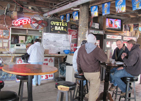 Flora-Bama Lounge Flora-Bama on Perdido Key is a classic roadhouse bar, complete with live music on three stages, and an oyster bar that serves them raw or Cajun-steamed, as well as peel-and-eat shrimp, and all things fried, including pickles. The slightly spicy gumbo, thick with okra and tomatoes, is laced with tiny shrimp. Located on the beach, a spit away from the Alabama border, it's where beach bums and bankers mingle. Save yourself a Northerner's embarrassment and pronounce it like the locals: Flora-Bama rhymes with the neighboring state, and not our president. - 17401 Perdido Key Drive, 850-492-3048, www.florabama.com
