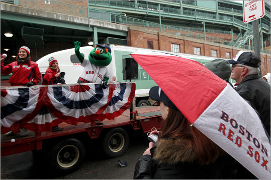 Jenney Griffin of Waltham stays dry under her umbrella as the Red Sox equipment truck was preparing to leave for Florida.