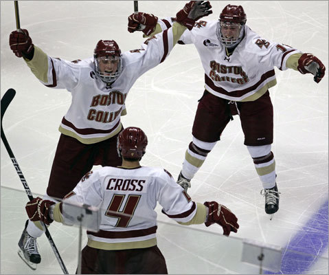 Boston College 3, Boston University 2 Boston College's Brian Dumoulin (left) and Pat Mullane (right) rushed into the waiting arms of teammate Tommy Cross (4) , who scored the game-winning goal in overtime to lift BC over Boston University in the first round of the 2011 Beanpot Tournament at TD Garden. BC won, 3-2.
