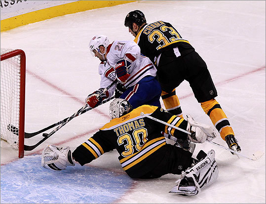 Thomas (30) made a save on a attempt by Canadiens right wing Brian Gionta (21). Bruins defenseman Zdeno Chara (33) lent a hand.