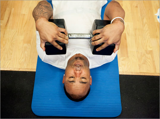 Crawford does sit ups with a 100-pound weight balanced against his chest.