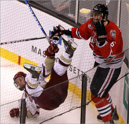 Boston College 7, Northeastern 6 Boston College's Cam Atkinson (left) was checked to the ice in the corner by Northeastern's Jamie Oleksiak in the third period.