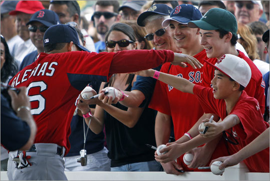 As he was coming off the field at the end of the workout, Red Sox shortstop prospect Jose Iglesias (left) heard the usual calls for autographs, but he gave an unexpected thrill to 12-year-old Collin Morowitz (far right) of Barrington, RI, when he ran over and gave him a big hug, then added to the thrill by giving the youngster his batting gloves out of his back pocket.