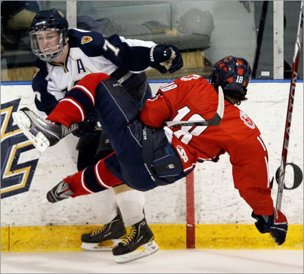 Malden Catholic's Brendan Collier checked Central Catholic's Josh Gallager (18) during the MIAA Super 8 hockey tournament in North Andover Saturday, March 5, 2011.