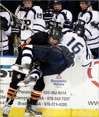 As his teammates looked on, St. John's Prep's Sam Kurker (16) was checked by Woburn's Brian Eliott.