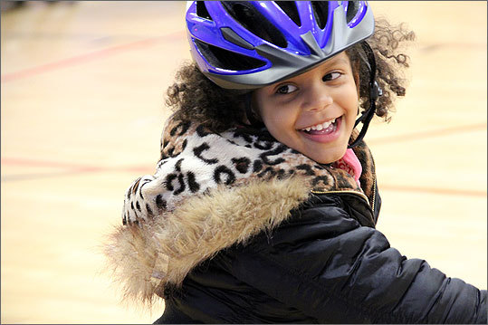 Helmet-wearing children, between ages 2 and 7, from the Orchard Gardens and Whitter Street developments inspected and tested out their fresh set of wheels at an event last Wednesday evening in the Orchard Gardens Community Center.