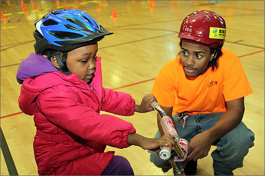 Members of Bikes Not Bombs, wearing orange T-shirts, trained the children skills for proper, safe bike use.