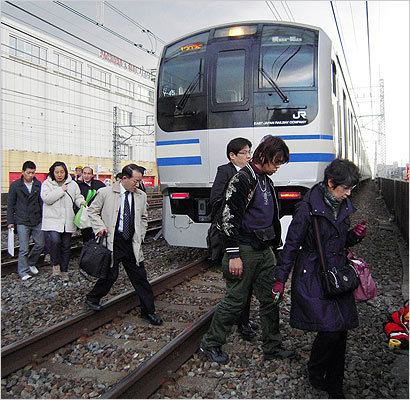 People walked on railway tracks as commuter train services were stopped in Tokyo.