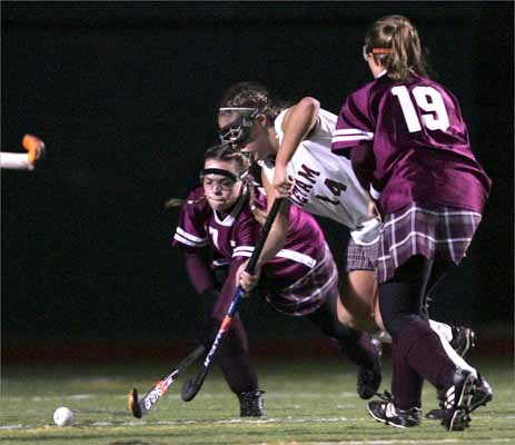 As a senior and center forward for Dedham High, Katie Kelly (in white) was named to the 2007 Girl's All-Scholastics field hockey team.