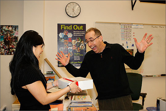 Steve Gordon, right, science teacher at John F. Kennedy Middle School in Waltham reacts as Jennifer Chan of Raytheon Company delivers some pie for 'Pi' Day.