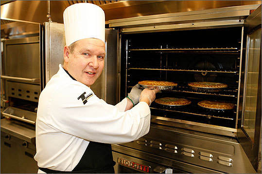Chef Skip Howell pulls some pies from the oven at Raytheon Company's Waltham headquarters.