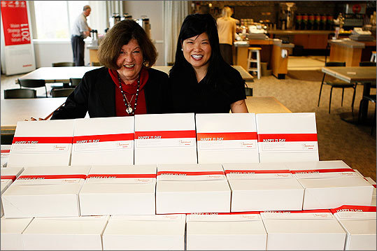 Luan Gilligan, left, and Jennifer Chan, both of Raytheon Company, build a pie pyramid for 'Pi' Day.