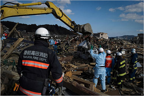 Japanese rescue workers dug through rubble in the city of Rikuzentakata, Japan, on Friday.