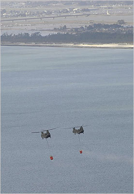 Japan Ground Self-Defense Force's helicopters hovered over off the coast of Natori, Japan, as they carried seawater to drop onto the Fukushima Daiichi nuclear plant on Thursday.
