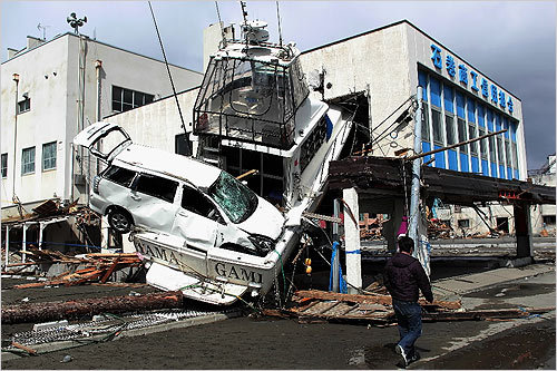 A man walked past a car wedged into a boat on Friday in Ishinomaki, Japan.