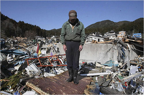 A survivor observed a moment of silence at the devastated town of Yamada in northeastern Japan on Friday.